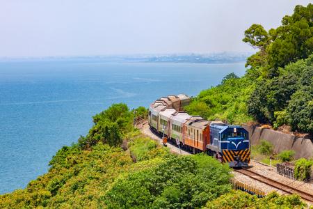 Tåg på järnvägen nära Fangshan Station i Pingtung, Taiwan