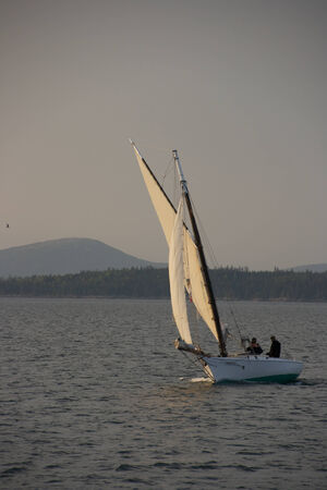 glimmer: A sailboat sailing in the evening sunset. Stock Photo