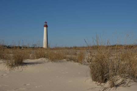 A sandy beach with a lighthouse in the background.