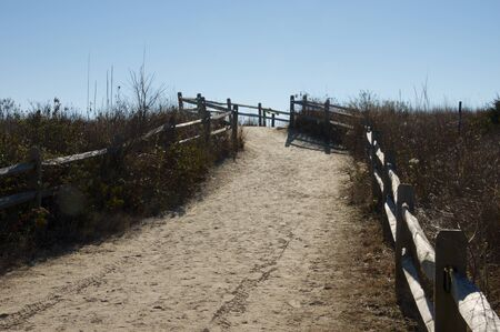 fenced in: A sandy trail fenced in by a rail fence leading to the beach. Stock Photo