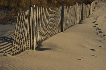 A sand fence in front of the dunes on the beach. Stock Photo