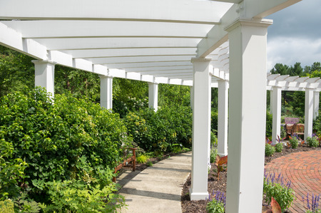 colonade: An arbor in a garden surrounded by bushes and flowers. Stock Photo