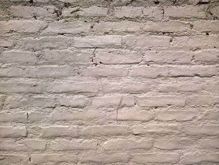 A brick wall painted in off white.