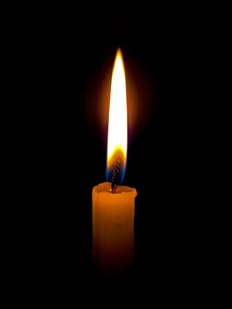 A candle burning in the darkness casting a warm glow.
