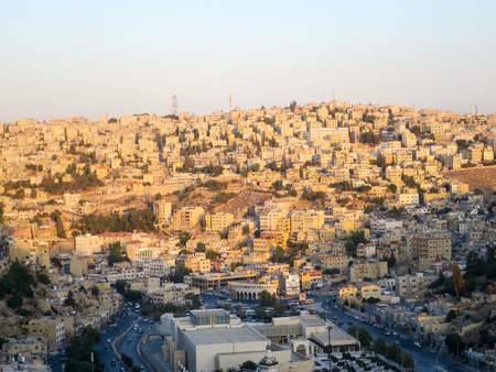 The scityscape of Amman, Jordan as the sun is setting and casting a warm glow over the city.