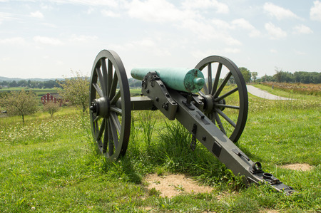 A cannon sitting on the top of a hill overlooking the broad flat valley.