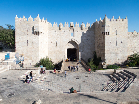 People going in and out of Damscus Gate in Jerusalem.