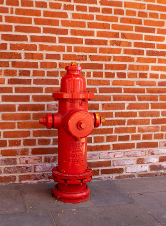A fire hydrant with a brick wall in the background.