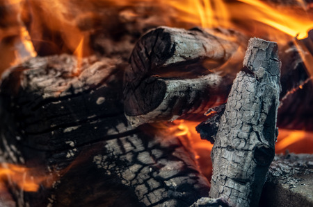 Firewood turning to coals in the fire.