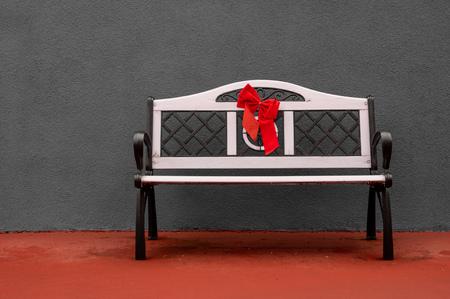 Un banc assis devant un mur de béton gris.