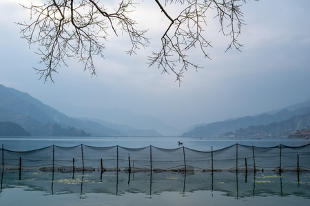 Some fishing nets on a lake with the Himalayan foothills in the background.