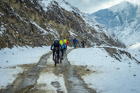 Some bicyclists biking on a snowy road in Nepal.