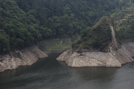 A steep rocky shoreline of a lake in nepal.