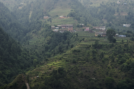 An old historic village on a hillside in Nepal surrounded by terraced fields.