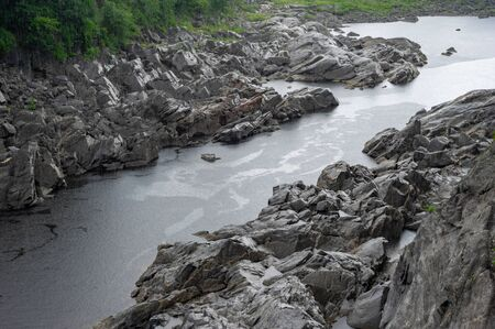 A rocky shoreline along the bank of a river as it is raining.