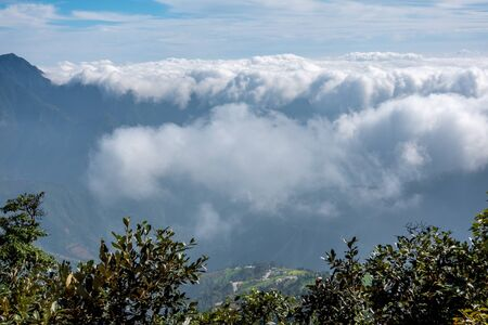A sea of clouds pouring over the mountain ridge. Stock Photo