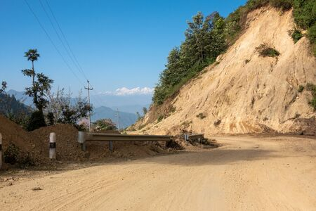A dirt mountain road with the Himalaya Mountains in the background.