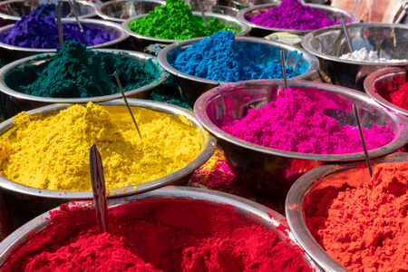 A table full of dishes of the colorful tikka powder.