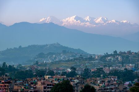 The Himalaya Mountains in the light of the setting sun above a small town.