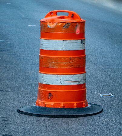 Un barril de construcción naranja sentado en la calle.