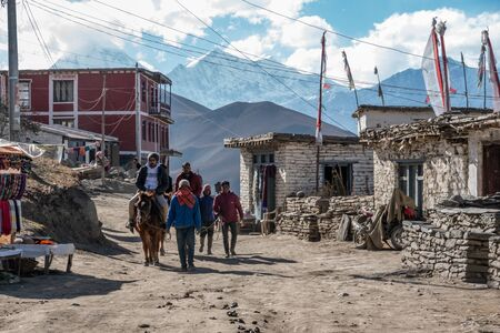Muktinath, Nepal - November 10, 2019: A man leading a horse with a man riding in the Himalaya mountains of Nepal.