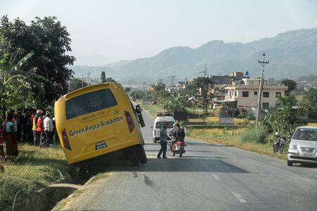 Pokhara, Nepal - November 8, 2019: A school bus filled with school students crashed into a ditch alongside the road in Nepal.