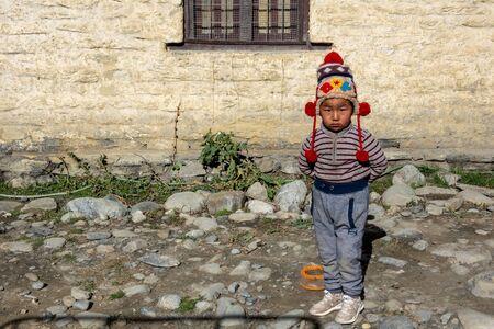 Mustang, Nepal - November 10, 2019: A yopung Nepali boy standing by the roadside in the Mustang region of Nepal.