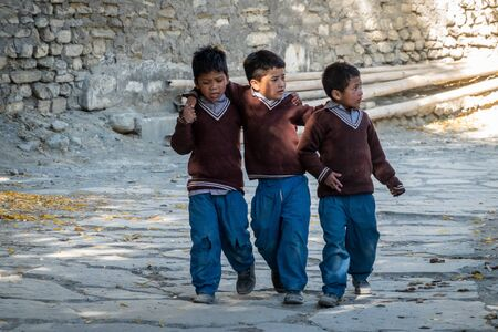Marpha, Nepal - November 11, 2019: Three schoolboys holding arms and walking down the road to school in Marpha, Nepal.