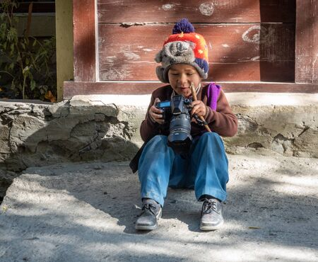 Marpha, Nepal - November 11, 2019: A young boy sitting on the ground and playing with a camera in Marpha, Nepal.