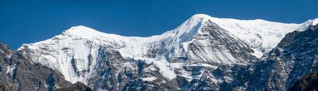 A panorama of the snow covered mountains of the Himalaya Mountain Range in Nepal. Trekking in the mountains of northern Nepal.