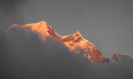 The late evening sun shining on the Himalaya snow peaks through a thick layer of clouds. Stok Fotoğraf