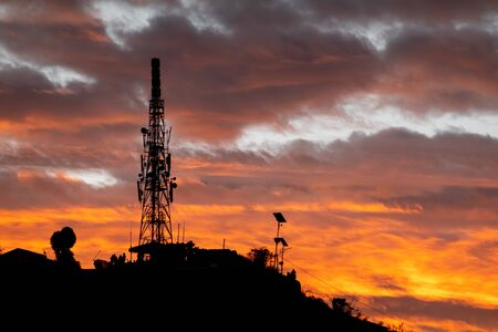 A cell phone tower or communications tower in the early morning sunrise. Stok Fotoğraf
