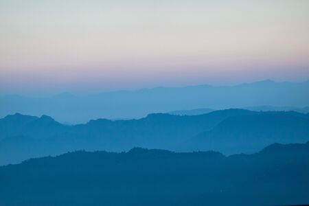 The beautiful colors of the evening sunset over the misty mountains. Stok Fotoğraf