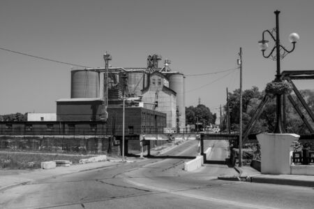 A collection of grain elevators beside some railroad tracks.