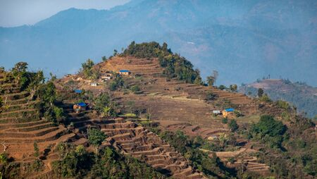 A few small village houses built on the hilltops of the Himalaya foothills of Nepal surrounded by terraced hillsides.