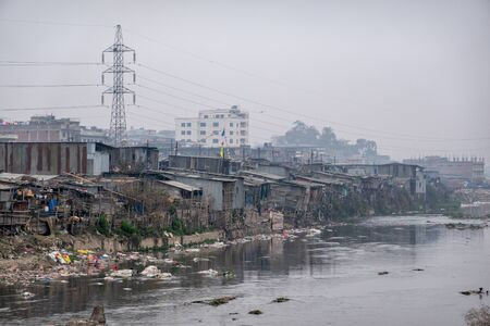 The dirt filled trash covered slums along the polluted Bagmati River in the city of Kathmandu while the smog is filling the sky.