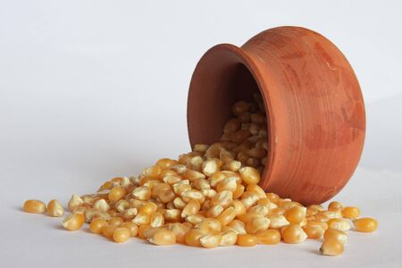 A small clay pot laying on its side with unpopped popcorn spilling out of it.
