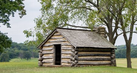An old log cabin perched on a hill under some trees.
