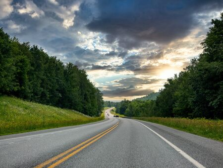 Traveling on the Open Highway in the Light of the Sunset surrounding by the forests of nature.