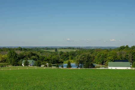 A Farm Nestled in the Valley beside a Pond surrounded by trees and green farmland.