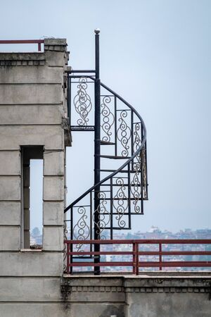 A Winding Metal Staircase on a Rooftop in portrait orientation.