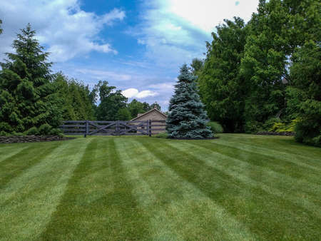 A freshly mown lawn with a barn in the background.