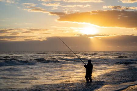 A fisherman fishing in the breaking waves along the seashore as the sun is rising in the morning.