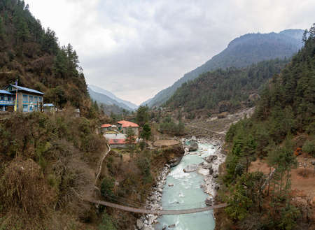 A small mountain town beside a river and swinging bridge in the mountains of Nepal. 免版税图像