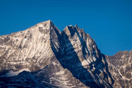 A snow covered mountain peak in the early morning light. 免版税图像