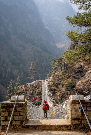 Person walking across the historic Tenzing Hillary suspension bridge on the trail to Mount Everest.