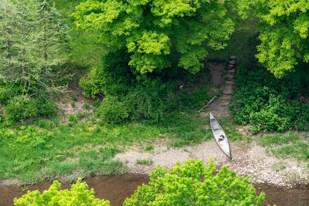 An aerial view of a canoe sitting on the bank of a creek.