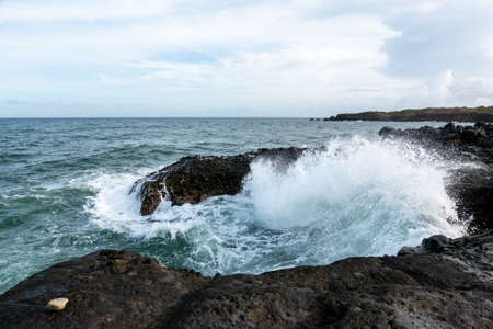 Waves crashing on the rocky shoreline of a small island.