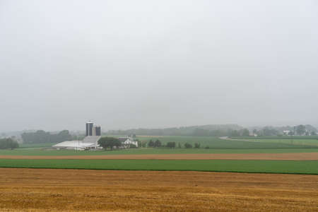 A farm in a valley surrounded by fields on a foggy morning.