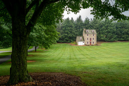 A historic stone house set on a freshly mown lawn.